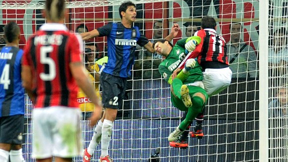 Inter goalkeeper Samir Handanovic is clattered after saving an attempt on goal from Gianpaolo Pazzini