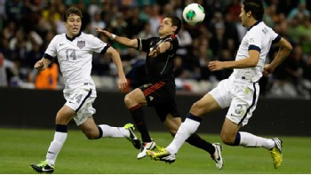 USA pair Matt Besler and Omar Gonzalez deal with Mexico striker Javier Hernandez