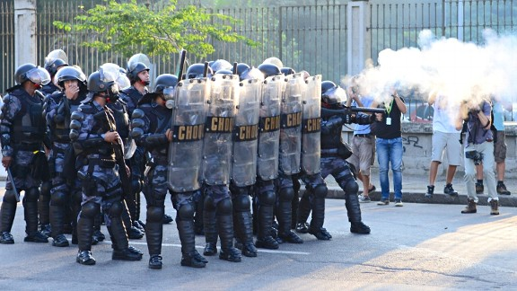Riot police clash with protesters outside of Maracana stadium.