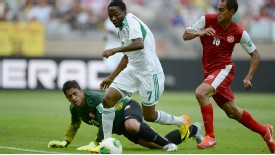 Nigeria's forward Ahmed Musa drives past Tahiti's goalkeeper Xavier Samin in their opening match