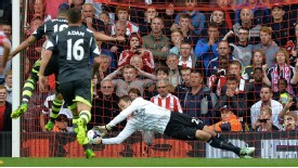 Liverpool goalkeeper Simon Mignolet saves Jonathan Walters' penalty.