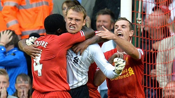 Simon Mignolet is mobbed after saving a penalty against Stoke.