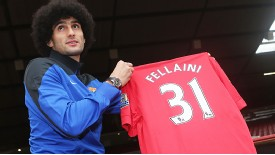Marouane Fellaini poses with a Man United shirt after being unveiled at Old Trafford.