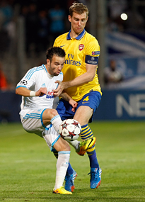 Arsenal's Per Mertesacker battles with Mathieu Valbuena.