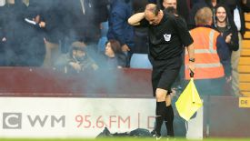 Linesman David Bryan feels the back of his neck after being hit by a smoke bomb thrown from the crowd.