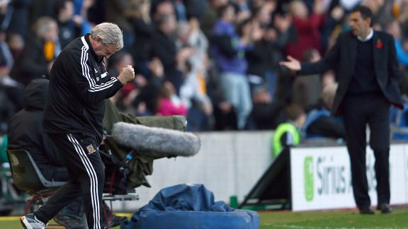 Hull manager Steve Bruce celebrates while Sunderland boss Gus Poyet looks on.