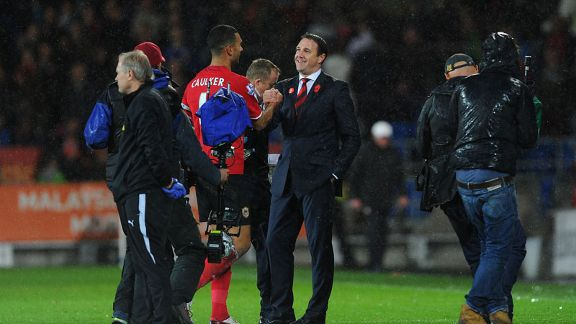 Malky Mackay celebrates Cardiff's win against Swansea with Steven Caulker.