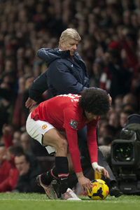 Marouane Fellaini is tackled by Arsene Wenger during Manchester United's win against Arsenal.