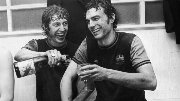 West Ham United's Pat Holland (left) and Trevor Brooking share a glass of champagne after a European Cup Winners Cup match in 1976.