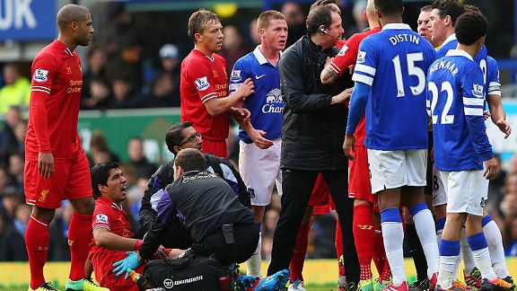 Luis Suarez gets treatment while the players argue over Kevin Mirallas' challenge.