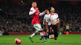 Alex Oxlade-Chamberlain challenges Luis Suarez in the area but referee Howard Webb said no penalty.