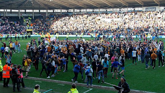 Hull City fans stage a pitch invasion to celebrate reaching Wembley in the semifinals of the FA Cup.
