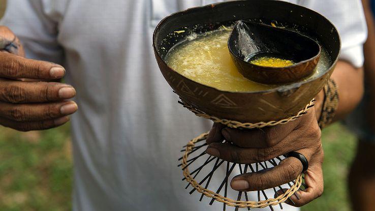 A football fan drinks a cassava soup during the final match of Peladao.