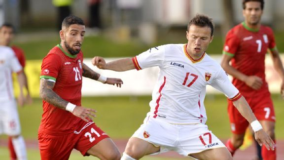 Ashkan Dejagah battles for the ball during Iran's goalless draw against Montenegro