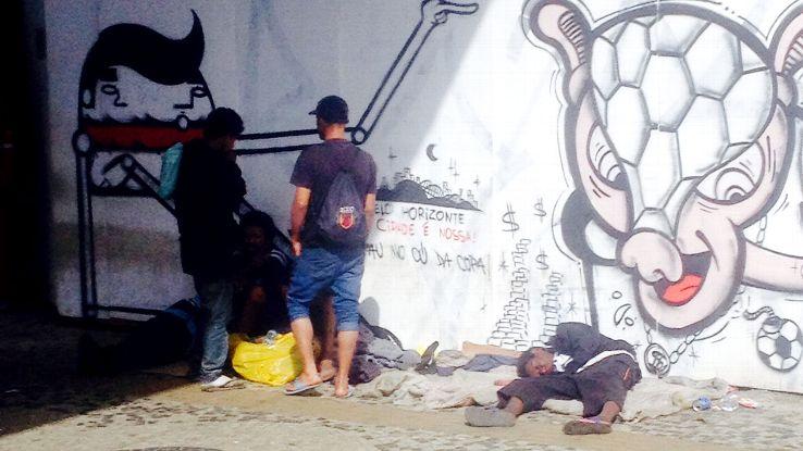 A homeless man sleeps beneath graffiti protesting the World Cup.