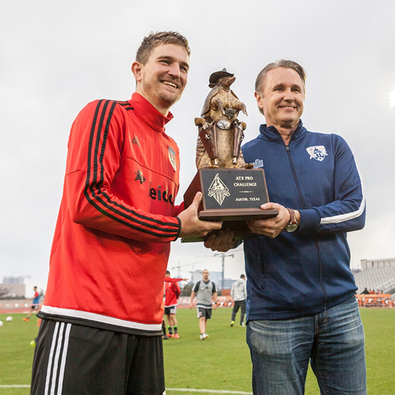 D.C. United defender Bobby Boswell, an Austin, Texas native, holds the armadillo trophy along with Austin Aztex owner and CEO Rene van de Zande.