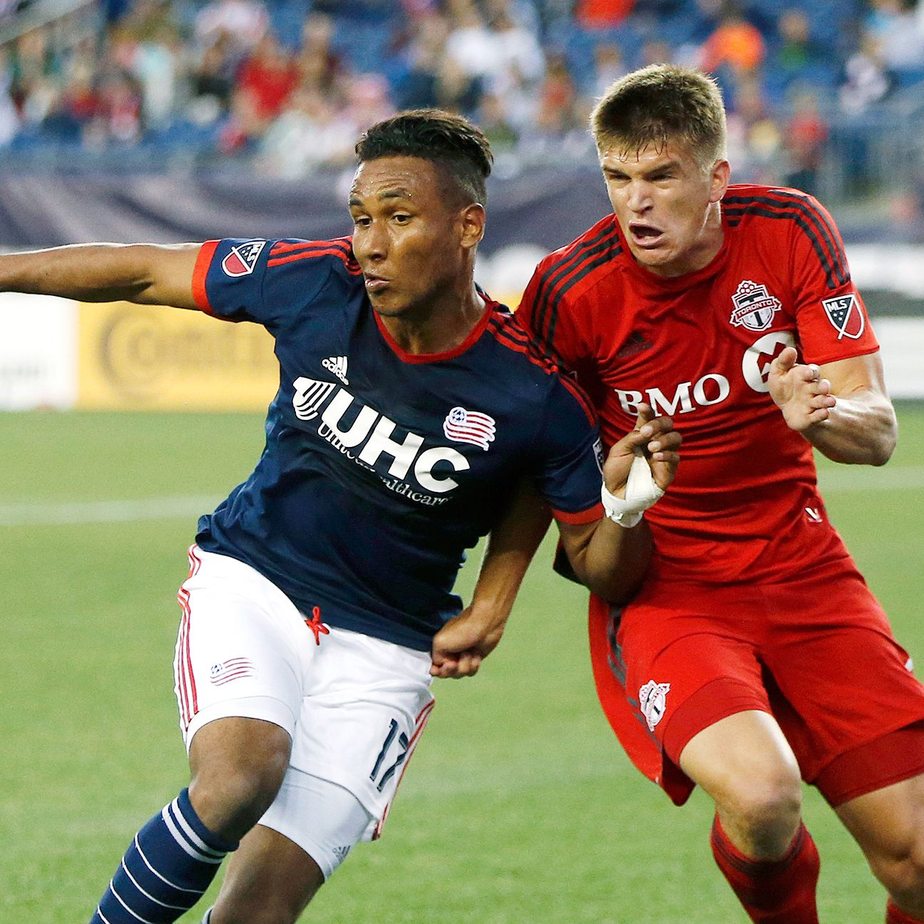 Toronto FC's Nick Hagglund (right) and the Revs' Juan Agudelo (17) battle for the ball during the first half.