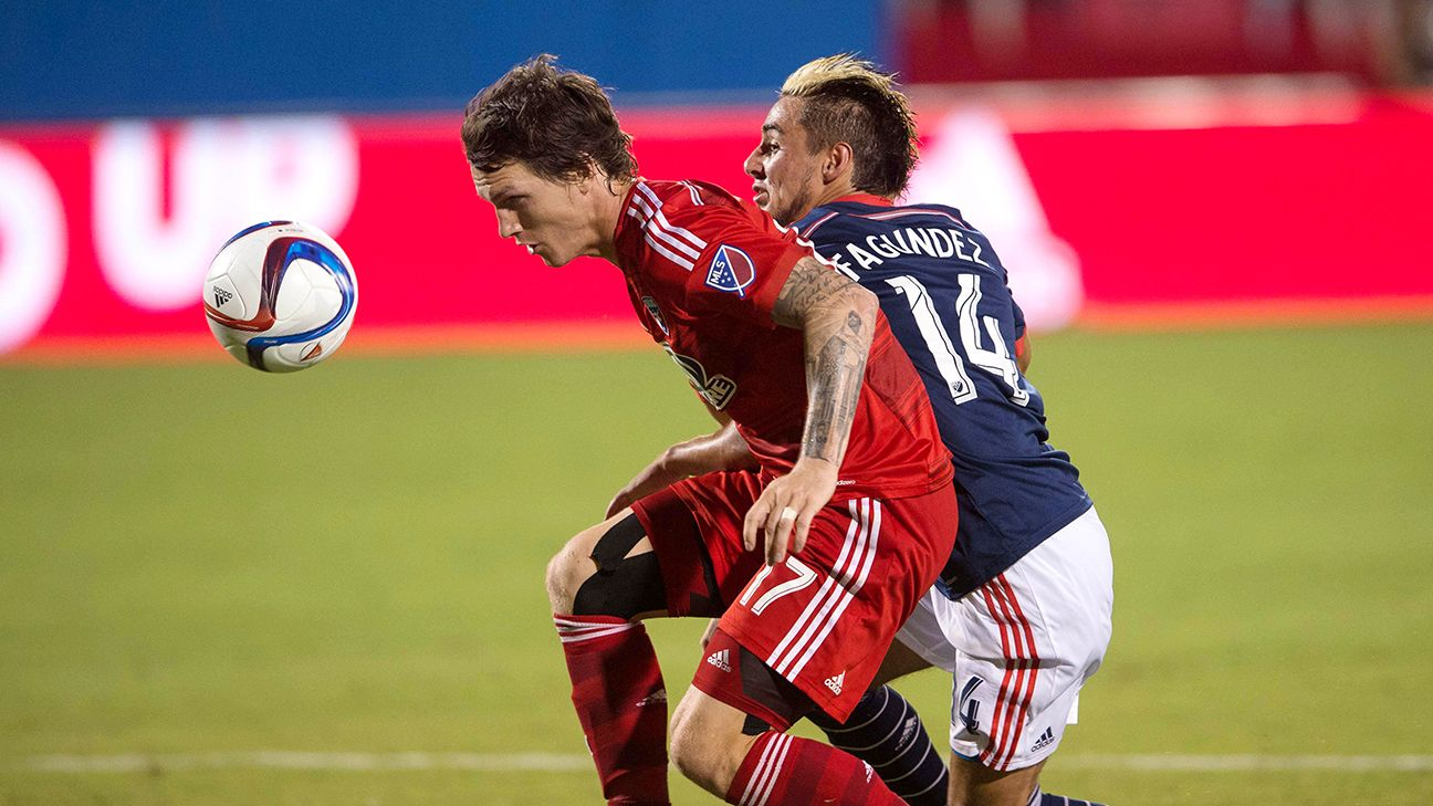 New England's Diego Fagundez fights for the ball against FC Dallas defender Zach Loyd during the second half of their teams' matchup on the Fourth of July.