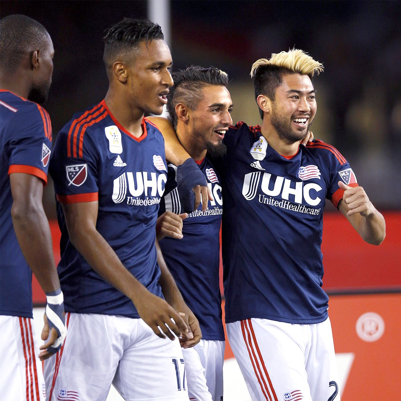 Diego Fagundez, center, celebrates his first-half goal with Lee Nguyen, right, and Juan Agudelo.