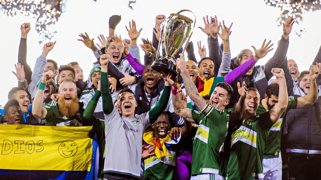 Timbers players hoist the MLS Cup trophy as they celebrate their victory.