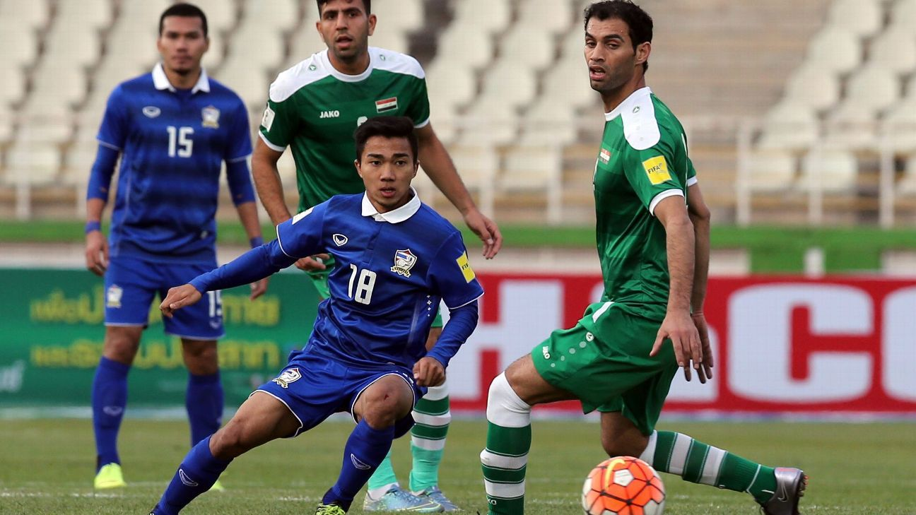 Thailand's Chanathip Songkrasin (C, #18) passes the ball past Iraq's Saad Abdul-Amir (R) during their 2018 World Cup qualifying football match