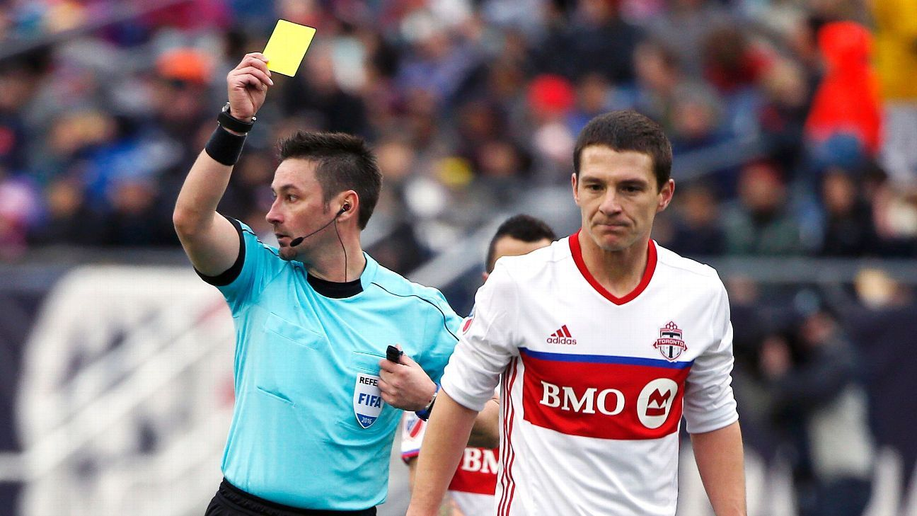 The referee gives a yellow card to Toronto FC's Will Johnson during the second half of an MLS soccer game against the New England Revolution in Foxborough, Mass., Saturday, April 9, 2016.
