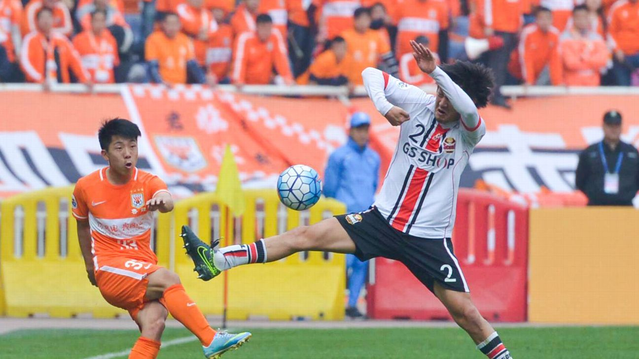 Jin Jingdao #33 of Shandong Luneng and Yojiro Takahagi #2 of FC Seoul compete for the ball during the AFC Champions League Group F match between Shandong Luneng and FC Seoul at Jinan Olympic Sports Centre on March 16, 2016 in Jinan, China.