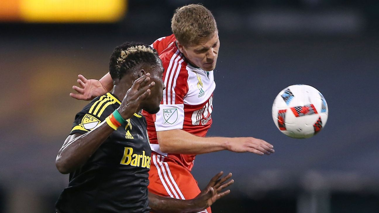 Crew midfielder Tony Tchani battles for the ball with Revolution midfielder Scott Caldwell in the first half.
