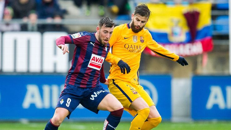 Sergi Enrich of SD Eibar duels for the ball with Gerard Pique of FC Barcelona during the La Liga match between SD Eibar and FC Barcelona at Ipurua Municipal Stadium on March 6, 2016 in Eibar, Spain.