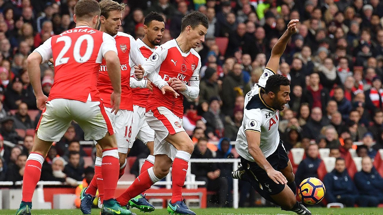 Arsenal defender Laurent Koscielny fouls Tottenham Hotspur midfielder Mousa Dembele.