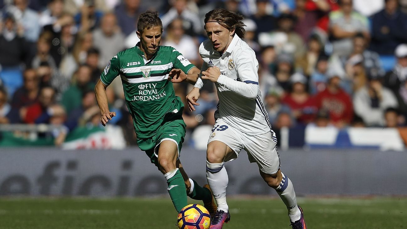 Luka Modric of Real Madrid competes for the ball with Alexander Szymanowski of Leganes.