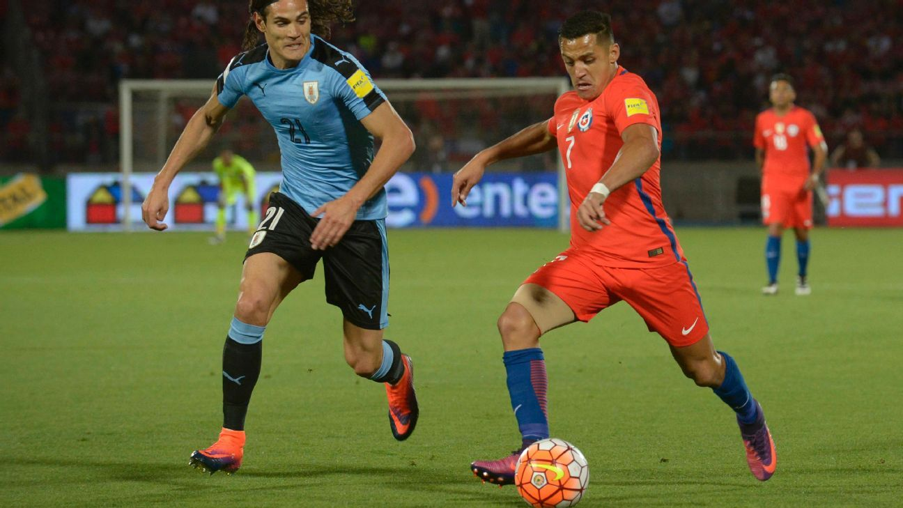 Alexis Sanchez battles for the ball with Edinson Cavani in Chile's 3-1 win against Uruguay.