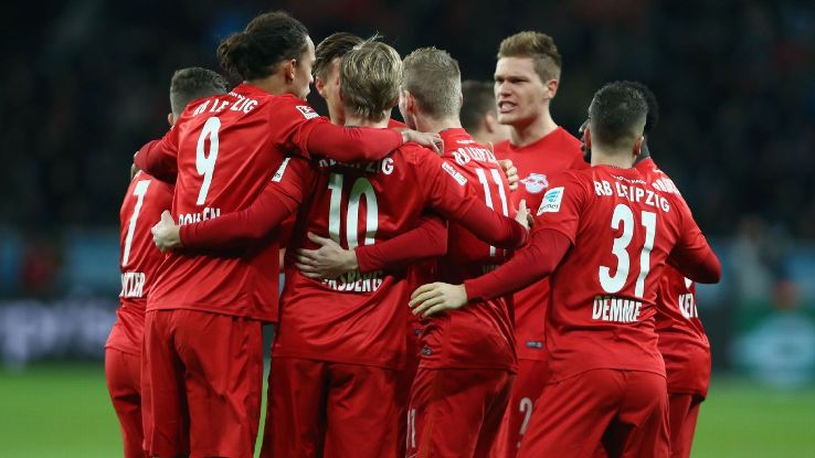 RB Leipzig players celebrate after scoring a goal against Bayer Leverkusen.
