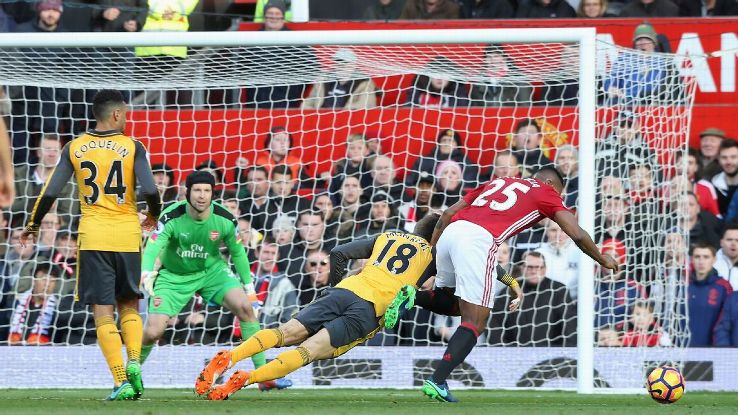 Antonio Valencia of Manchester United contests the ball with Arsenal's Nacho Monreal.