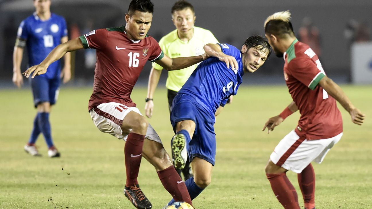 Philippines' Misagh Bahadoran of Philippines, tackled by Fachruddin Wahyudi Aryanto and Zullham Malik Zamrun of Indonesia