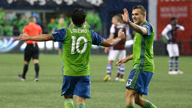 Seattle Sounders forward Nicolas Lodeiro, left, is greeted by forward Jordan Morris, right, after Lodeiro scored a goal against the Colorado Rapids on a penalty kick during the second half of the first leg of the MLS soccer Western Conference finals, Tues