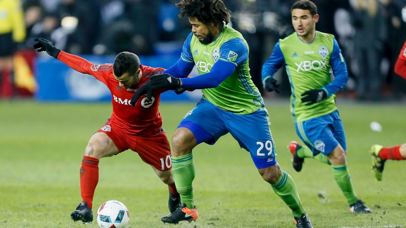 Sebastian Giovinco and Roman Torres battle for the ball in the MLS Cup final between Seattle and Toronto.