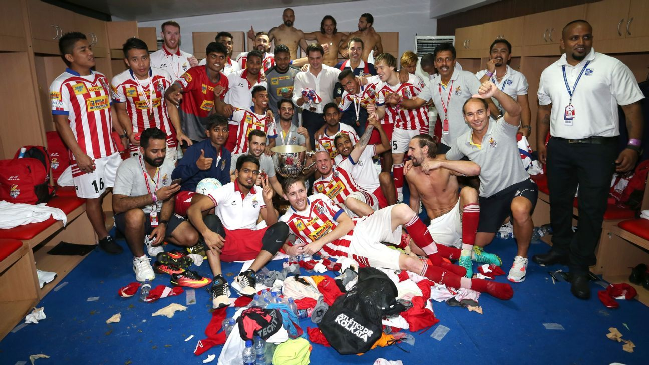 Atletico players celebrate winning the ISL in the change room.
