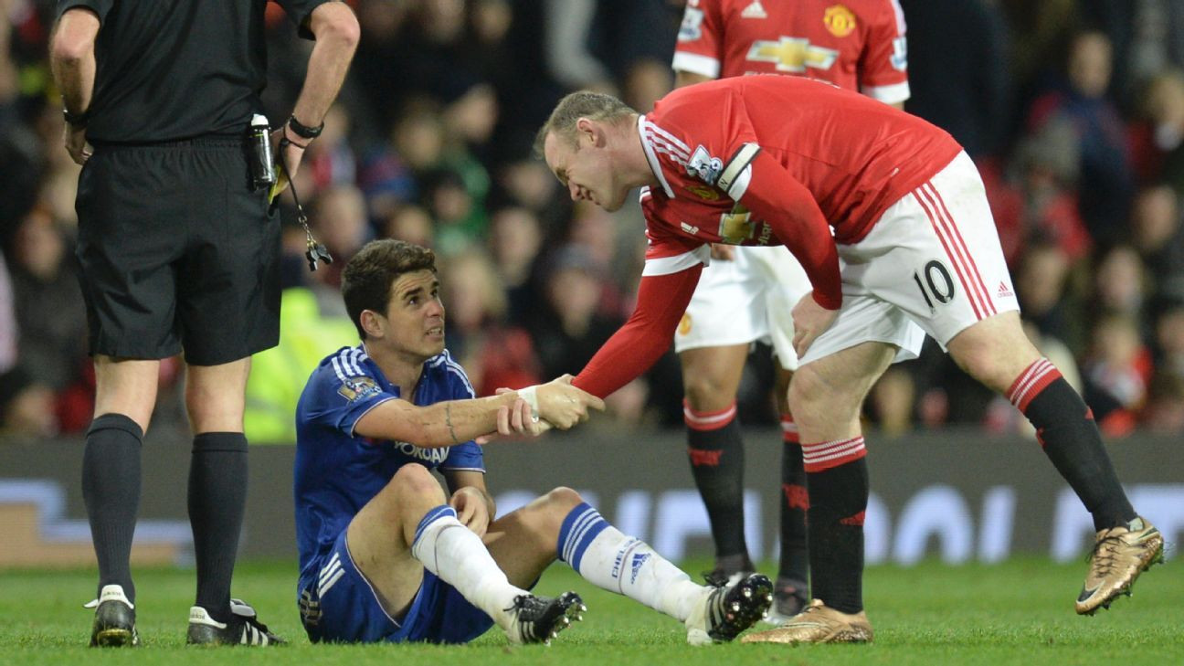 Wayne Rooney (R) helps up Oscar (C) after fouling him in a challenge that earned Rooney a yellow card during the Premier League football match between Manchester United and Chelsea at Old Trafford on December 28, 2015. AFP PHOTO / OLI SCARFF