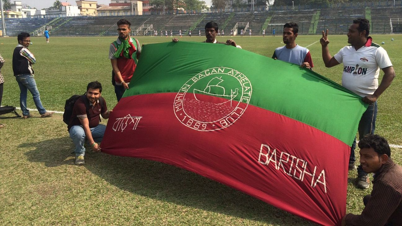 Fans pose with a Mohun Bagan flag at Siliguri's Kanchenjunga Stadium ahead of Sunday's Kolkata derby.