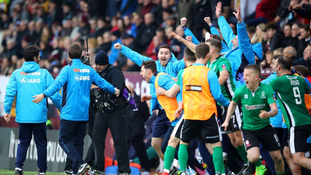 The Lincoln City bench celebrate the final whistle