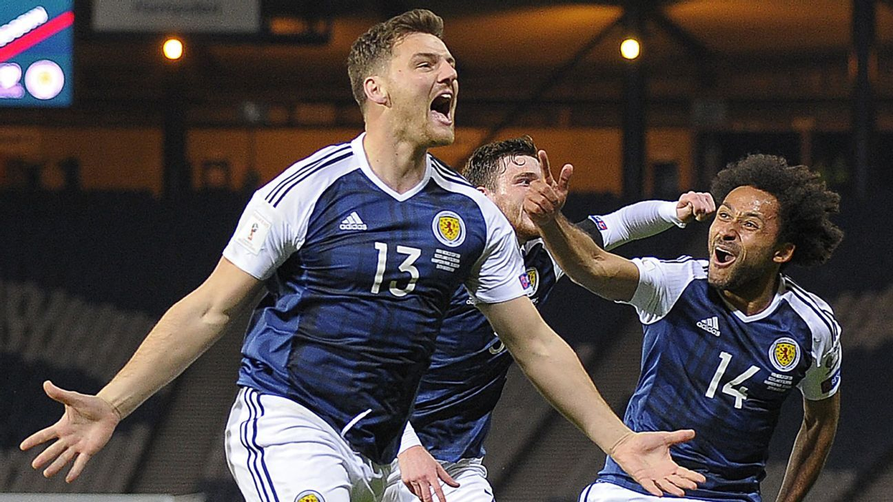 Chris Martin, left, celebrates after scoring a dramatic winner for Scotland against Slovenia.