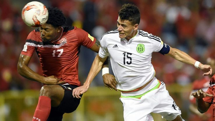 Hector Moreno battles for the ball with Mekeil Williams in Mexico's World Cup qualifier against T & T.