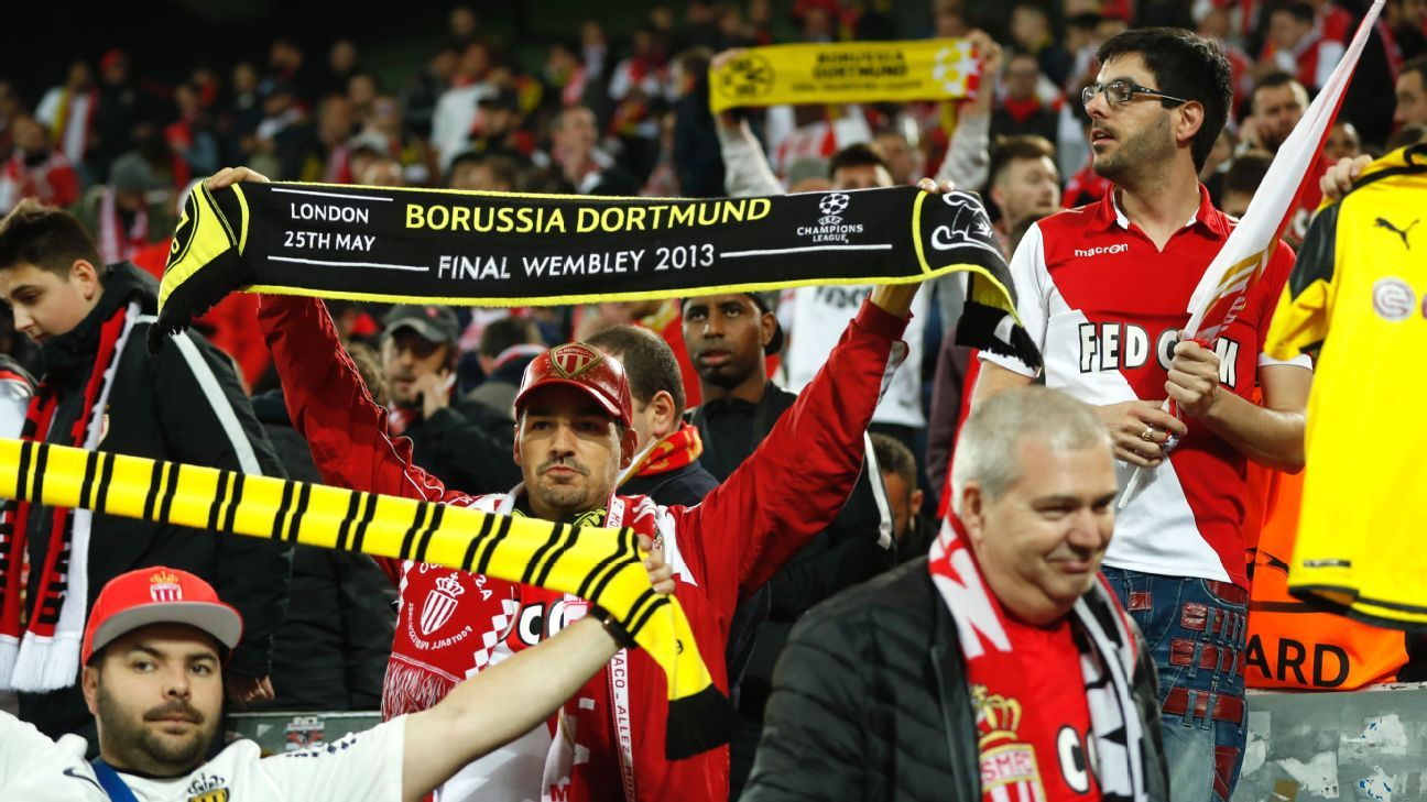 Monaco supporters with Borussia Dortmund scarves react in solidarity after their Champions League quarterfinal match was postponed.