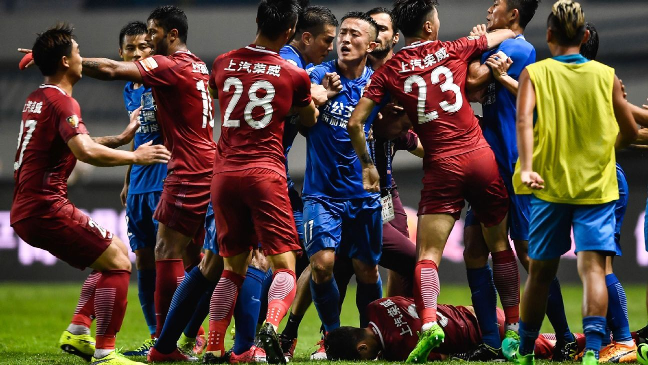 Shanghai SIPG and Guangzhou R&F players fight in the Chinese Super League as Oscar lays on the ground.