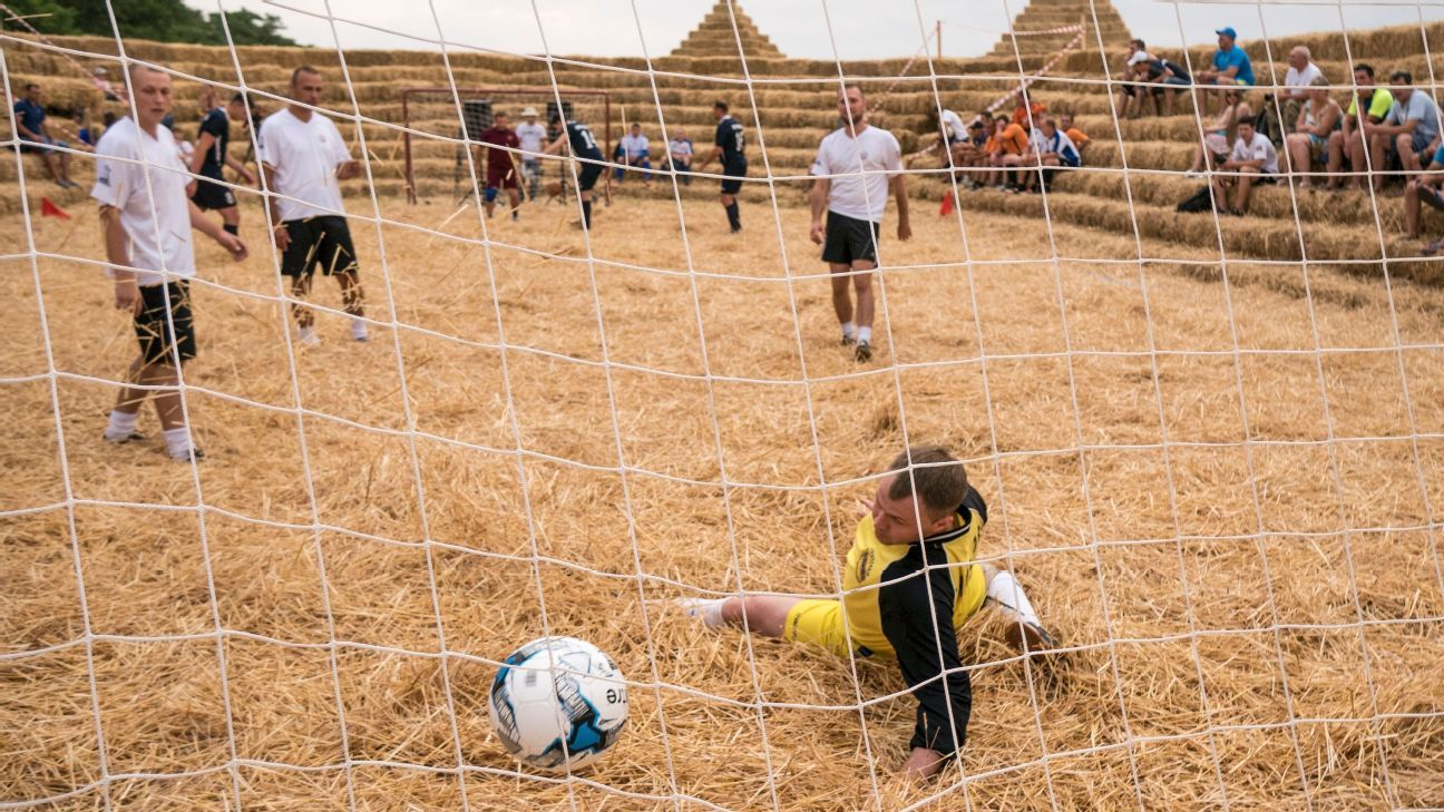 The goalkeeper looks on as the ball agonisingly rolls past him on the straw pitch
