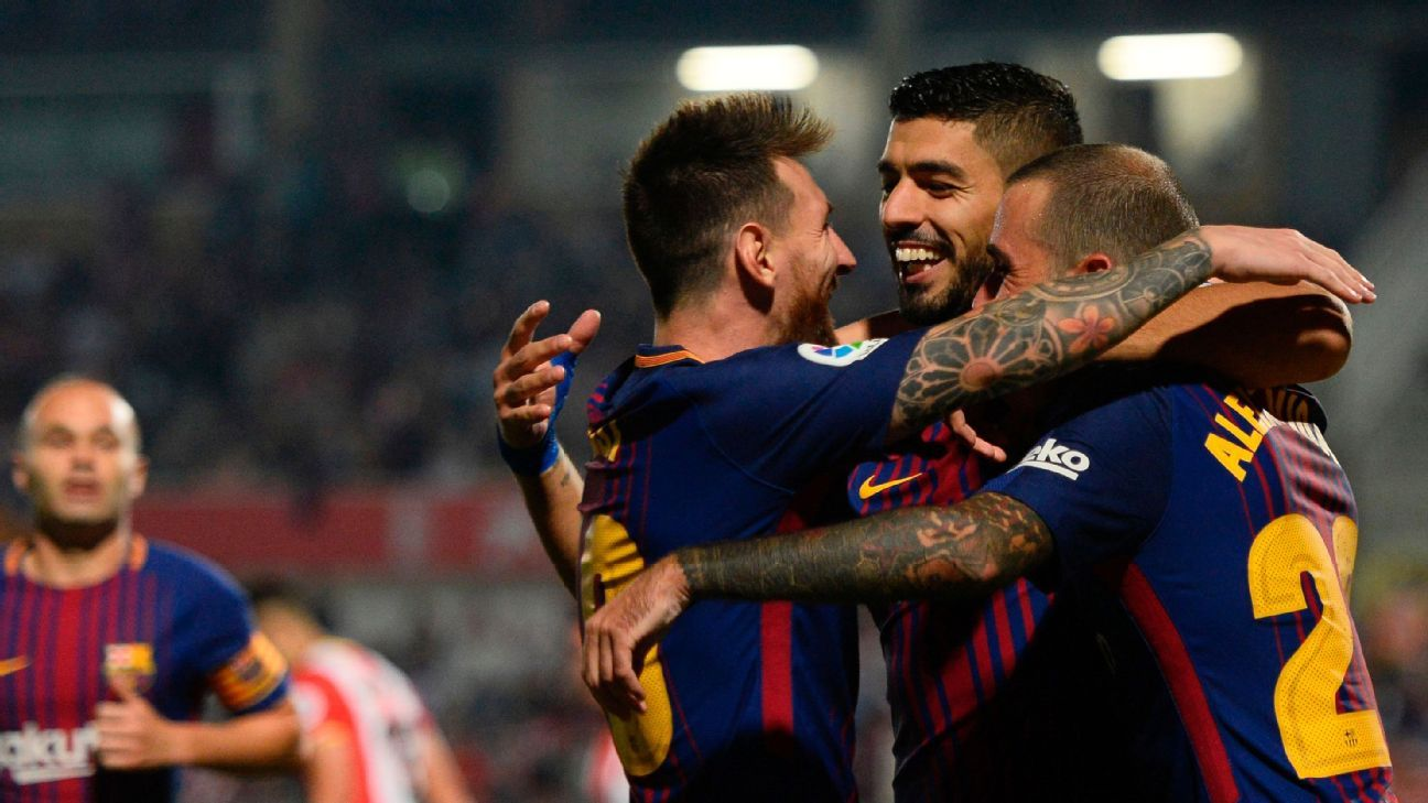 Barcelona teammates celebrate after scoring their third goal in a La Liga win against Girona.