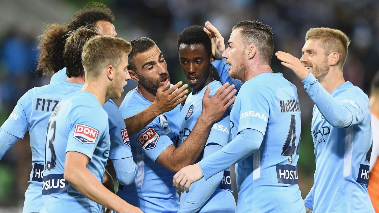 Bruce Kamau is mobbed by Melbourne City teammates after scoring.