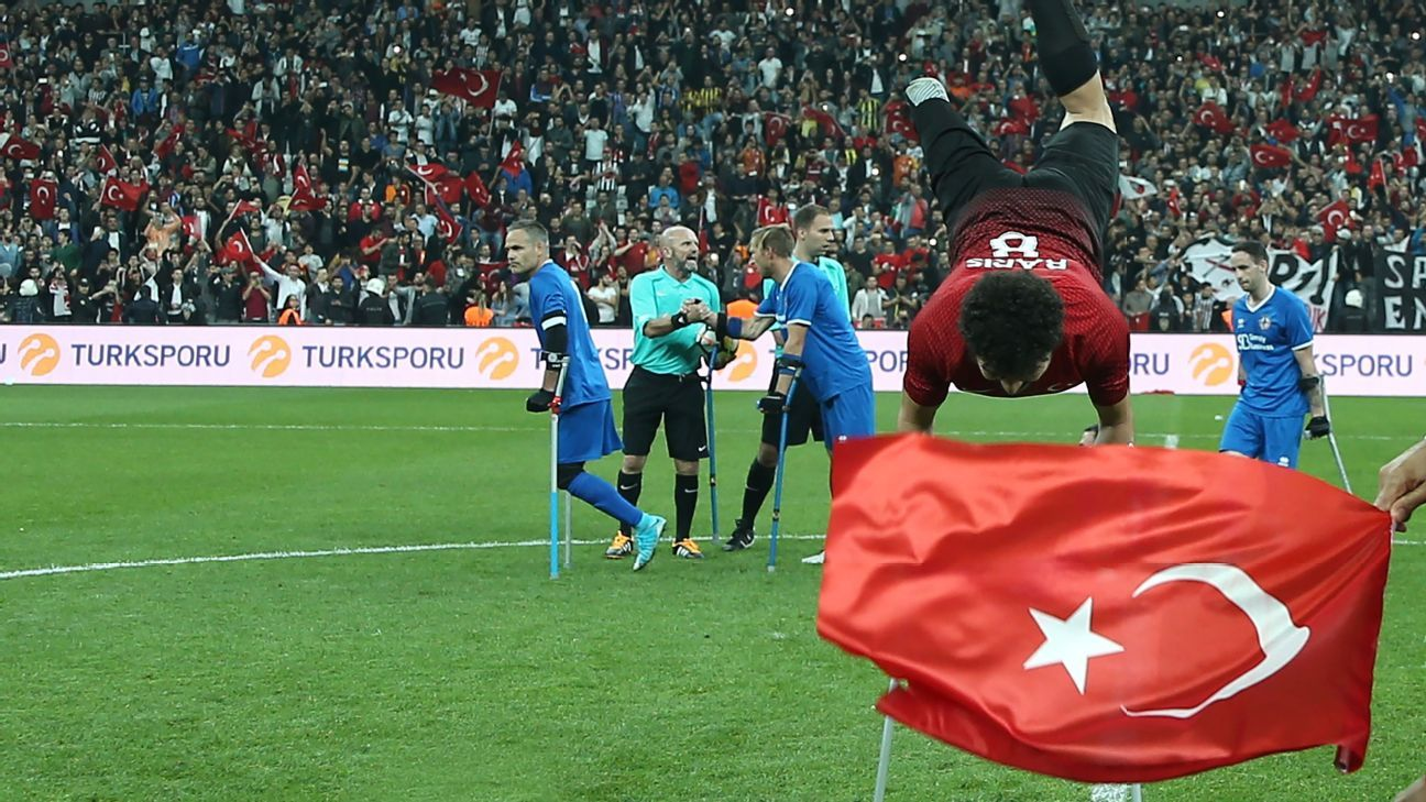 Baris Telli celebrates in front of a Turkish flag