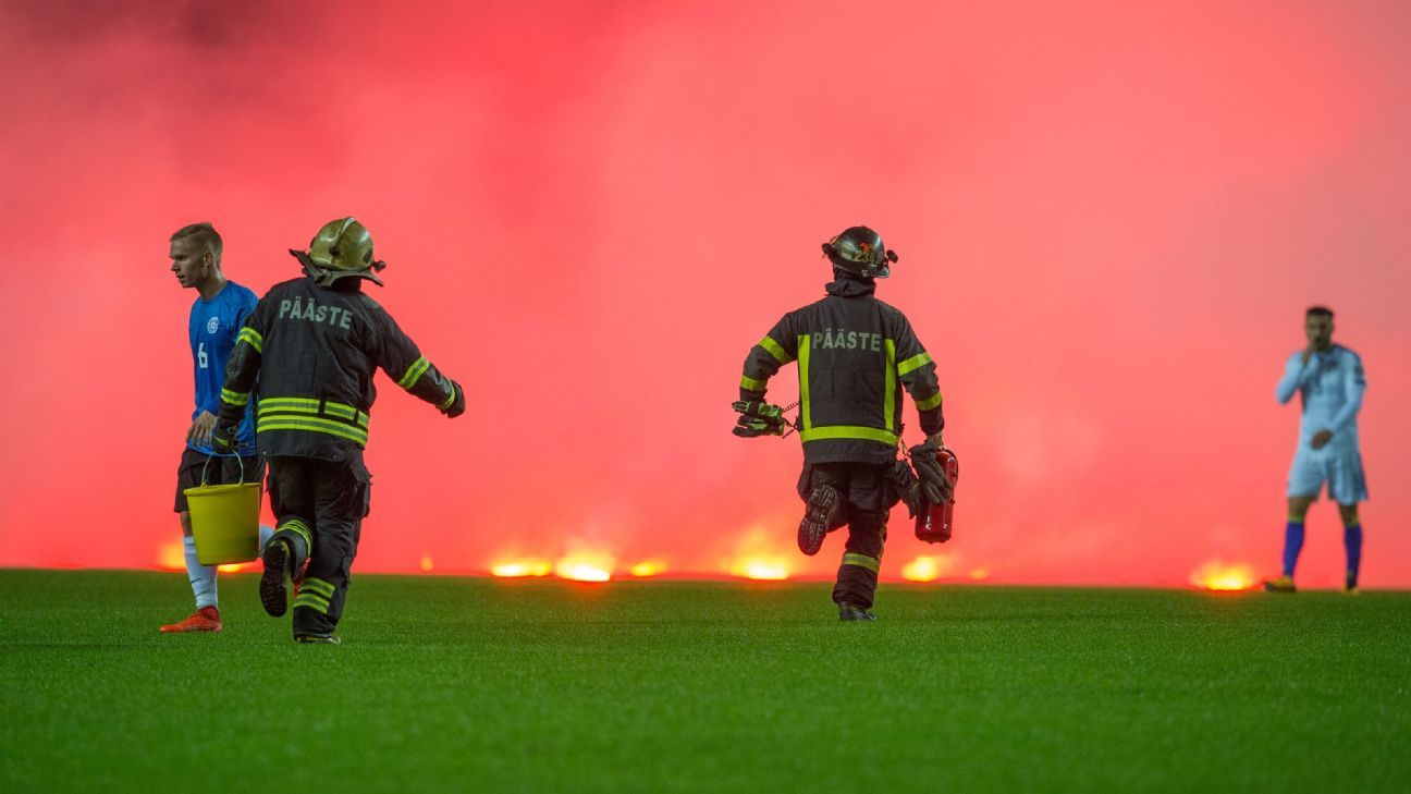 Firefighters run on the pitch to take care of flares thrown by Bosnia fans during World Cup qualifier in Estonia